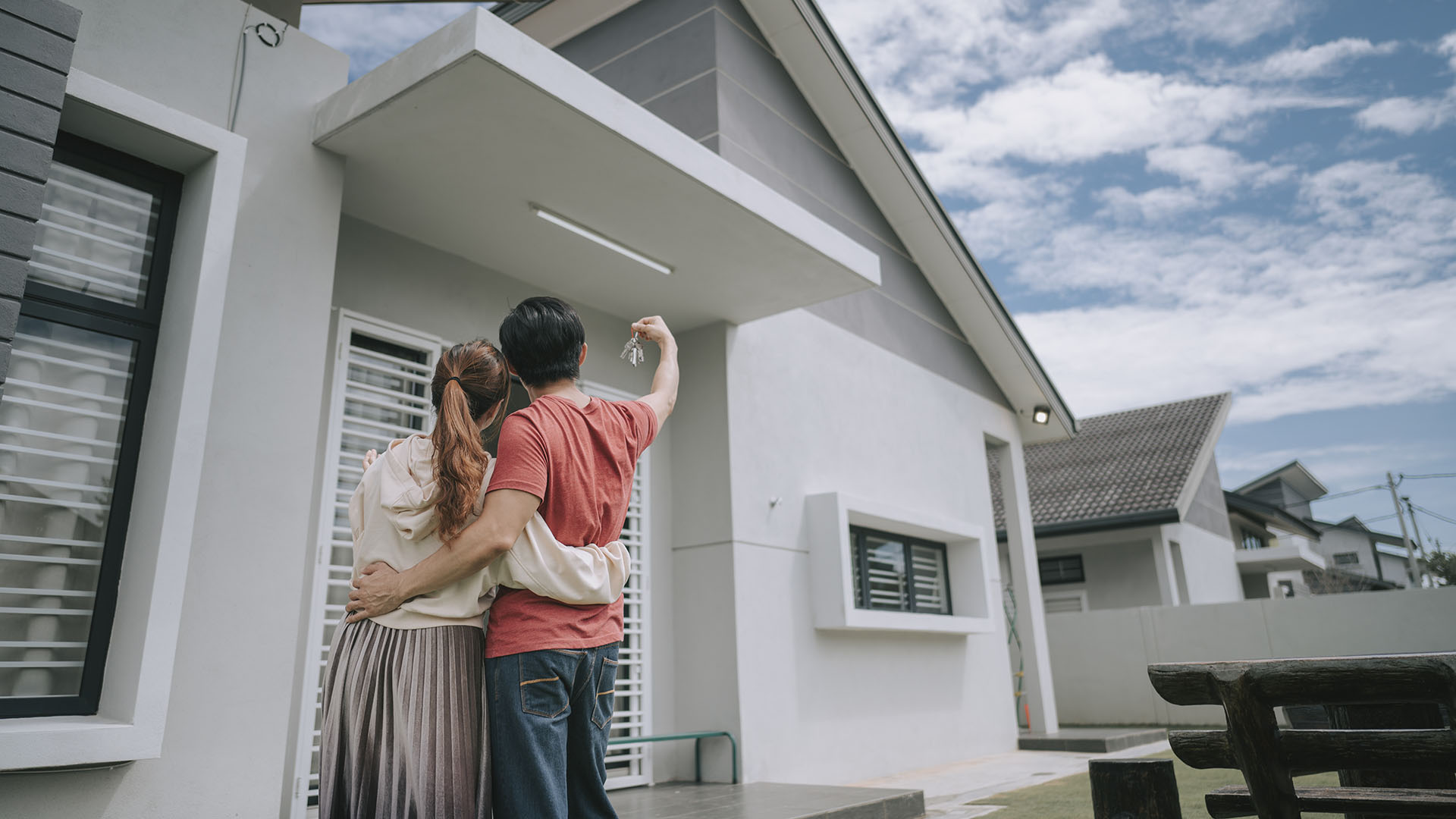 A couple posing outside their newly bought house, the home they are both financially committed to